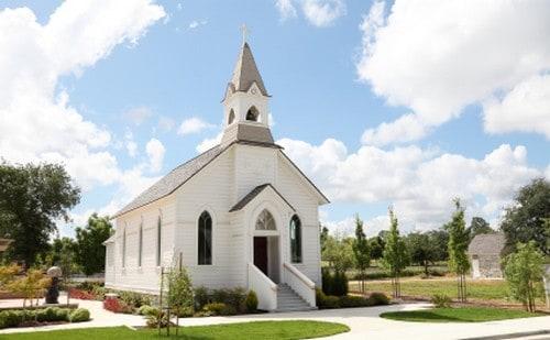 Small white church house under a blue sky.