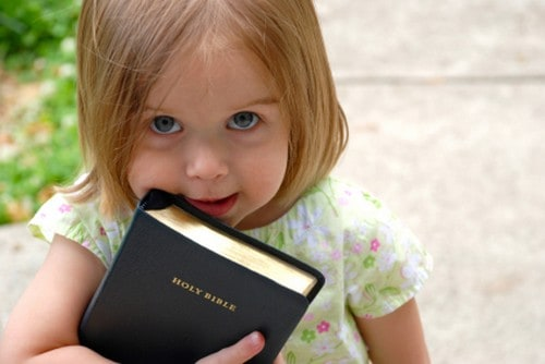 Little girl holding Bible