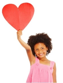 Girl holding up paper heart.