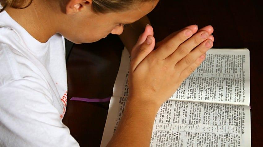 young-girl-praying-open-bible